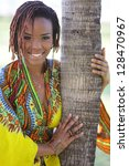Stock image of a young black woman posing by a palm tree - stock photo