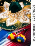 Pair of wooden maracas and sombrero on a bright poncho, vertical shot - stock photo