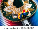 Traditional mexican sombrero and maracas on a striped poncho - stock photo