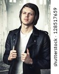 portrait of a young man in a black leather jacket - stock photo