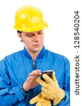Portrait of a young construction worker using mobile phone isolated on white background - stock photo