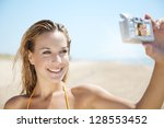 woman on the beach, photographing herself with digital camera - stock photo