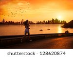 Young woman running at sunset - stock photo