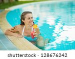 Happy young woman at pool with cocktail looking on copy space - stock photo