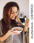 smiling woman enjoying her bowl ...   Shutterstock . vector #128788523