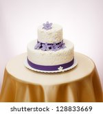 White wedding cake with violet marzipan flower decoration - stock photo