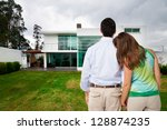 Young couple watching new big house - stock photo