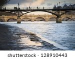 Small photo of Passerelle des Arts over River Seine in Paris, France. Silhouettes of people walking on it. Pont Neuf (the oldest bridge in Paris) in the distance.