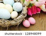 Springtime Easter nest with eggs and flowers over a wood background - stock photo