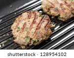 Homemade beefburgers, or beef patties, cooking in a ridged grill-pan - stock photo