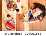 A young adult woman cutting fruits in the kitchen. - stock photo