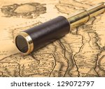 Vintage brass telescope on antique map - stock photo