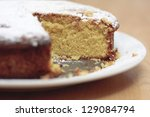 A home baked lemon drizzle cake with a slice missing - stock photo