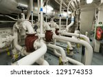 Industrial valves, pipes in ship's engine room - stock photo
