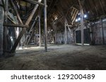 Old wooden barn with light shining through the wooden boards - stock photo