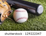 A baseball over green grass with bat and glove - stock photo