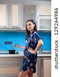 young housewife cooks food in modern kitchen - stock photo