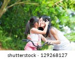 Asian child kissing her mother. Asian family having fun outdoor, biking outdoor. - stock photo