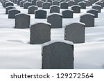 The cemetery in winter with gray granite tombstones in the snow - stock photo