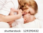 happy family. baby and mother play, kiss, tickle, laugh in white bed - stock photo