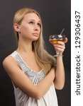 Vertical shot of a cheerful celebrating girl with a glass of drink - stock photo