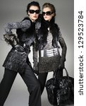 Two fashion model wearing sunglasses holding purse posing - stock photo