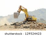 A large trackhoe or tracked excavator  moving rock from a hill at an airport runway expansion project - stock photo