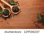 Stock photo dry tea with green leaves in wooden spoons on wooden background 129530237