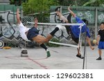 BANGKOK - AUG 20: Takraw players compete in an informal street match on derelict land Aug 20, 2012 in Bangkok, Thailand. Takraw or sometimes Kick Volleyball is one of the national sports of Thailand. - stock photo