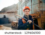 Portrait young man in a helmet worker standing with a hammer on the shoulder - stock photo