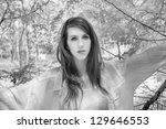 infrared portrait of a young woman standing in a wooded area. - stock photo