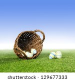 wicker basket with decorated easter eggs in grass. Ground fog in the background. Clear blue sky for copy space - stock photo