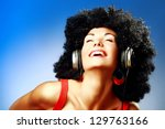 Happy woman with afro haircut enjoying music in headphones - stock photo