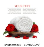 Rolled white towel and roses and rose petals on a white background - stock photo