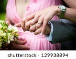 Young married couple holding hands with wedding bouquet - stock photo