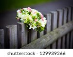 Wedding bouquet with roses and freesia on rustic country fence - stock photo