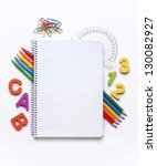 Blank notebook surrounded by a border of various school supplies - stock photo