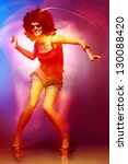 Sexy woman with afro haircut is dancing disco. Disco 80 style. - stock photo