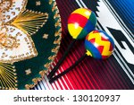 Mexican sombrero and maracas on traditional poncho, studio shot - stock photo