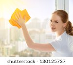 happy young woman housewife washes a window - stock photo