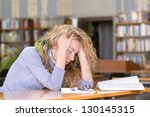 sad student  working in library - stock photo