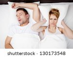 Snoring man and young woman. Couple sleeping in bed. - stock photo
