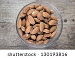 Top view of glass bowl full of almonds - stock photo