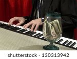 man playing piano with tips jar on piano - stock photo