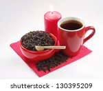 Red ceramic dishes with black tea and a burning candle - stock photo