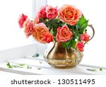 Beautiful fresh roses in a vintage jug . - stock photo