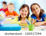 Portrait of two diligent girls looking at camera at workplace with schoolboys on background - stock photo