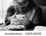 Black and white shot of woman's hands holding cup of coffee - stock photo