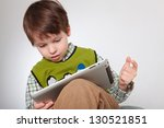 CCute little boy with a tablet pc - stock photo