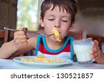 Cute little boy having delicious breakfast - stock photo
